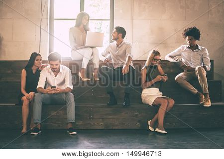 Students life. Group of cheerful young people communicting while holding different gadgets and sitting close to each other on steps