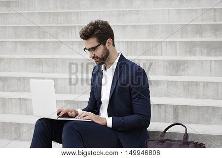 Businessman working on laptop sitting on steps
