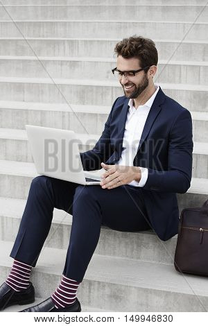 Businessman with glasses using laptop and smiling