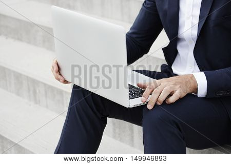 Businessman with laptop dedicated to work close up