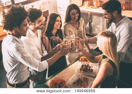Cheers to old friends! Top view of cheerful young people cheering with champagne flutes and looking happy while having party on the kitchen