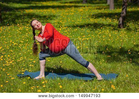 Pregnancy yoga exercise - pregnant woman doing asana Utthita parsvakonasana outdoors on grass in summer