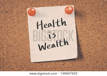 Health is Wealth. note message on a bulletin board