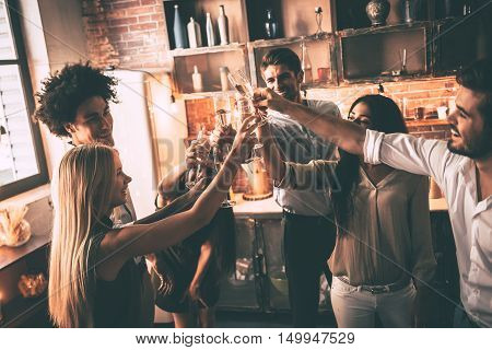Cheers! Top view of cheerful young people cheering with champagne flutes and looking happy while having home party
