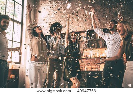 Confetti fun. Group of happy young people throwing confetti and jumping while enjoying home party on the kitchen