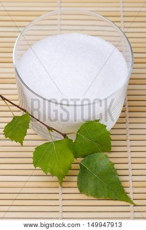Xylitol birch sugar in a glass bowl with birch leaves on a bamboo mat. White granulated sugar alcohol, substitute used as sweetener that taste like table sugar, extracted from the wood of birch trees.