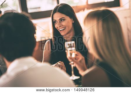 Dinning with friends. Cheerful young people enjoying food and drinks while sitting together at home