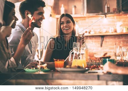 Dinnier with friends. Cheerful young people enjoying meal while sitting at the dinning table on the kitchen together