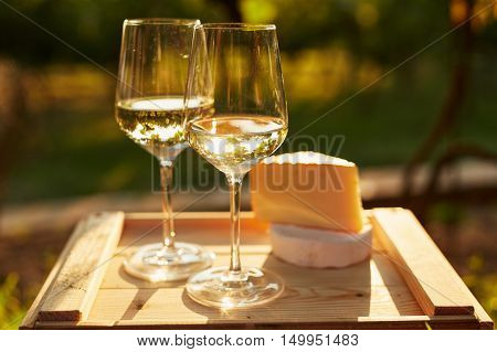 Two Glasses Of White Wine With Cheese On Wooden Box, Toned At Sunset
