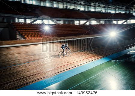 Athlete with a bicycle at velodrome