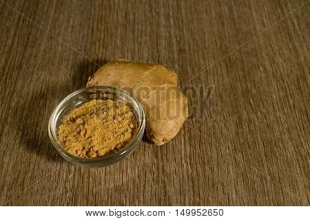 Raw ginger and its powder on a wooden background