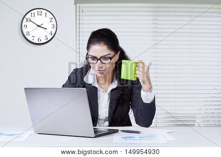 Indian young businesswoman looks busy working in the office while enjoying a cup of coffee and using a laptop
