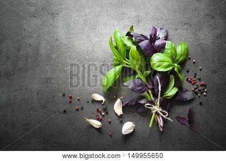 Basil leaves garlic pepper at dark slate background. Fresh herbs