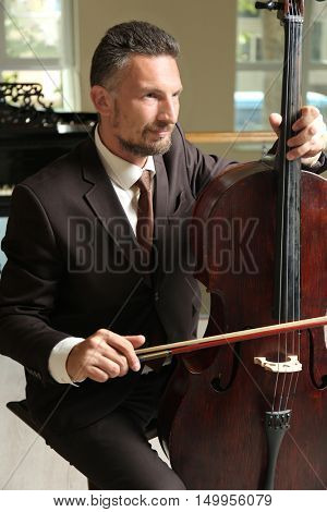 Man playing cello in room