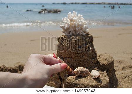 Girl is making a Sandcastle with coral and seashell on sandy beach