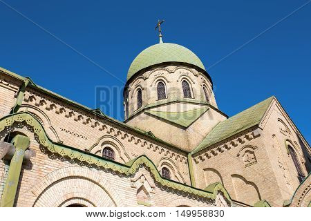 Dome of orthodox church with a cross. dome of green color against the sky