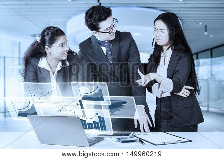Three young multiethnic businesspeople discussing in the office with virtual financial graph on the laptop