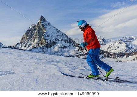 Ski touring man reaching the top in Swiss Alps. Matterhorn in the background, Zermatt, Switzerland.