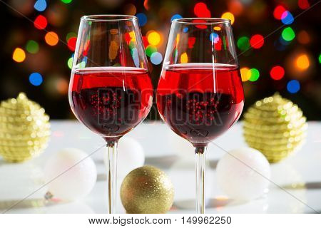 Red wine glasses and christmas balls on the bright background