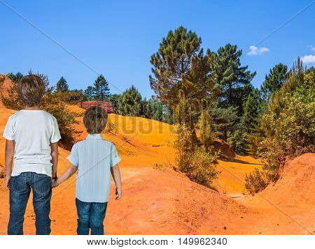 Two boys of seven and four years admired the nature. Orange and red picturesque hills. Languedoc - Roussillon, Provence, France