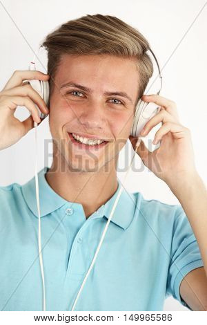 Portrait of a young man listening to music; isolated on white