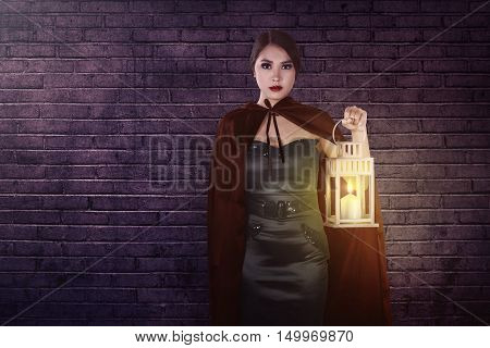 Beautiful Asian Witch Woman Standing Behind The Wall Holding A Lantern
