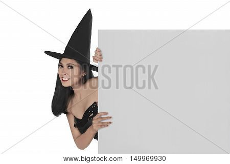 Young Smiling Asian Woman With Hat In The Witch Costume Holding Blank Board