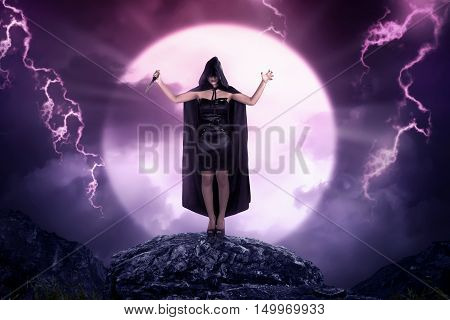 Pretty Asian Witch Woman With Cloak Holding Sharp Knife