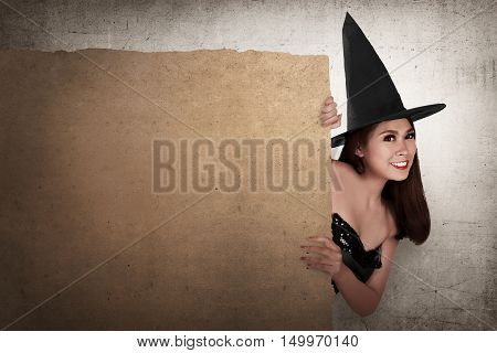 Beautiful Smiling Asian Woman With Hat In The Witch Costume Holding The Parchment