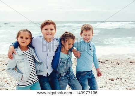 Group of fashion children wearing denim clothing having fun on the sea shore. Autumn casual outfit in blue and navy color. 7-8 years old models.