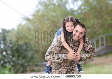 US army soldier with little daughter in park