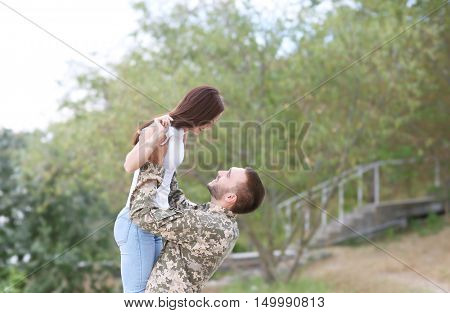 Happy US army soldier with wife in park