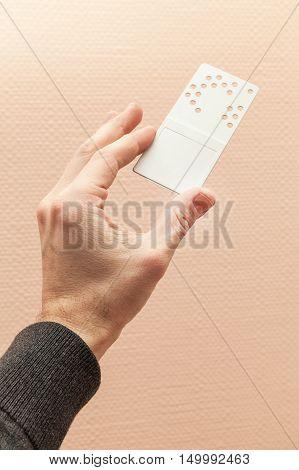 Male Hand Holds Gray Plastic Door Key