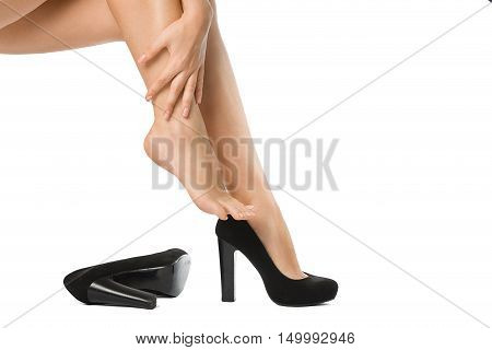 Woman unshoed her legs. Bare legs of the woman with her hand isolated on white. Beautiful skin. Foot care
