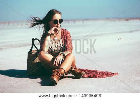 Fashion model wearing bohemian chic clothing posing on the salt beach outdoor.