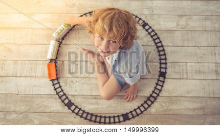 Top view of cute little boy playing with toy train looking at camera and smiling