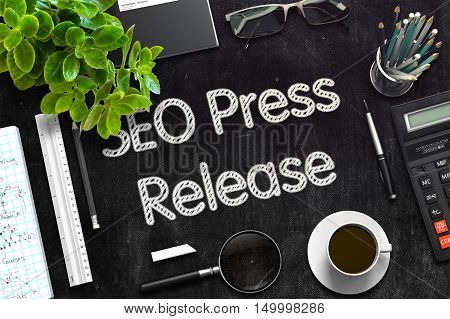 SEO Press Release - Black Chalkboard with Hand Drawn Text and Stationery. Top View. 3d Rendering. Toned Illustration.