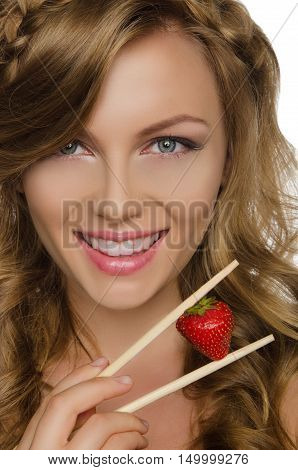 pretty woman holding strawberry with chopsticks isolated on white