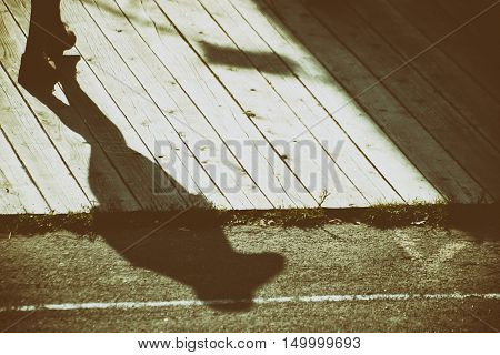 The shadow of a woman with boot shoes on a wooden platform.
