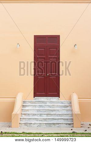 Ancient wooden brown door on orange wall