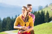 Couple in Tracht on Alp mountain summit at vacation poster
