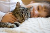 A girl and her cat taking a nap together. poster