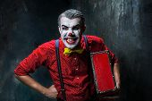 Terrible clown and Halloween theme: Crazy red clown with suitcase on a dark background poster
