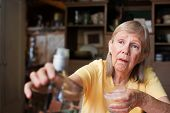 Lonely senior adult female reaching for a bottle of liquor while holding a glass poster