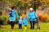 Happy senior lady with a walker or wheel chair and children. Grandmother and kids enjoying a walk in the park. Child supporting disabled grandparent. Family visit. Generations love and relationship. poster