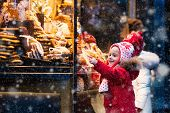 Children window shopping on traditional Christmas market in Germany on snowy winter day. Kids buying candy pastry and gingerbread in confectionery. Boy and girl choosing sweets in Xmas bakery. poster