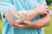 Man wearing elbow brace to reduce pain poster