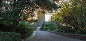 Vorontsov palace park, Alupka, Crimea. Turret and fortress wall with gate. Sundown, sun shines through the green foliage, cropped bushes. Scottish Baronial, Mughal architecture, Gothic Revival architecture styles. poster