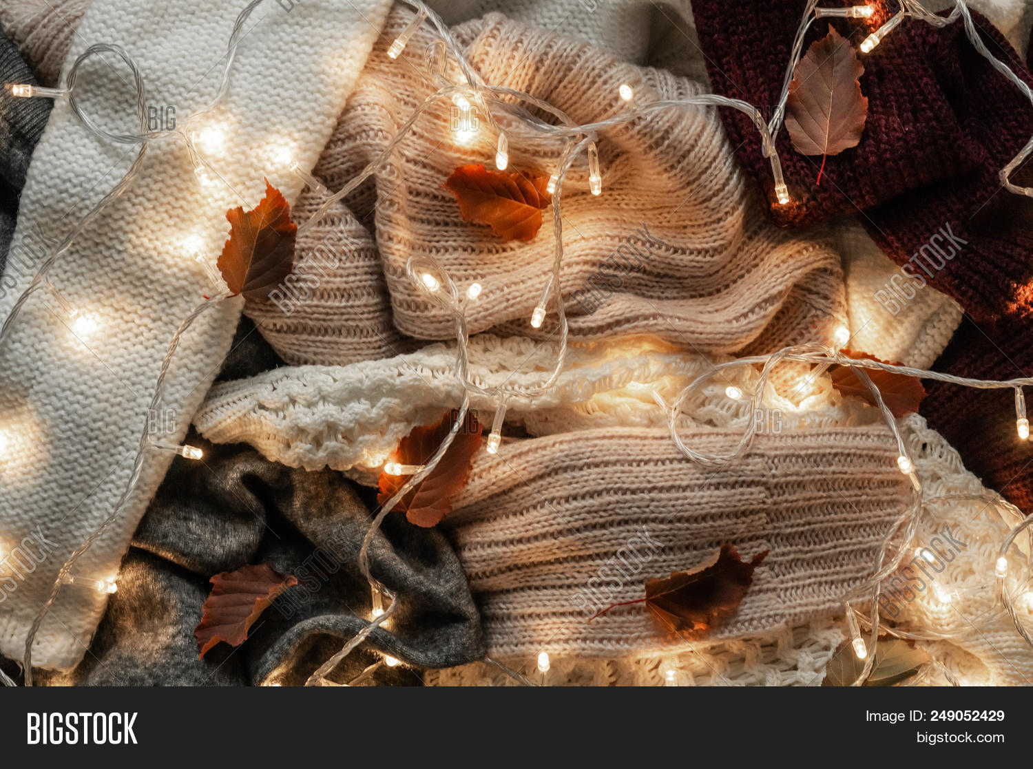 bac79df721 Background With Warm Sweaters. Pile Of Knitted Clothes With Autumn Leaves  And A Garland