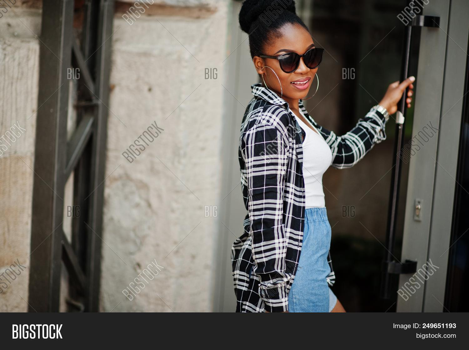d29dcc94595 Hip hop african american girl on sunglasses and jeans shorts. Casual street  fashion portrait of black woman.